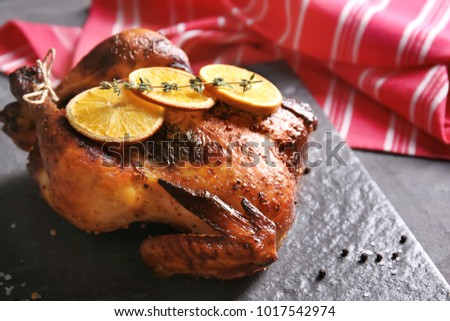 Delicious whole roasted chicken with orange served on slate plate