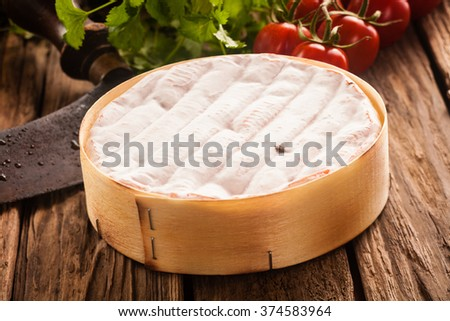 Delicious whole uncut ripe French camembert cheese in a box on a rustic wooden table with herbs and fresh salad ingredients - stock photo