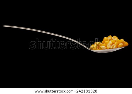 Delicious, yellow, canned corn in a silver spoon on a black background. - stock photo