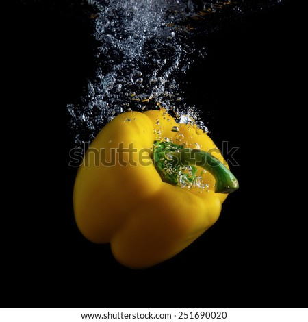 Delicious yellow sweet pepper in water with air bubbles. Photo on black background. - stock photo