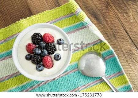 Delicious yogurt and fresh berries for breakfast with strawberries, blackberries and blueberries served on a colourful striped placemat - stock photo