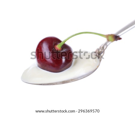 Delicious yogurt in spoon with cherry isolated on white