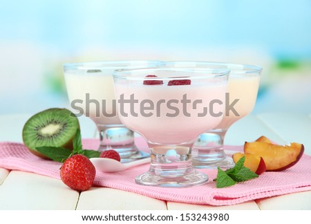 Delicious yogurt with fruit and berries on table on bright background