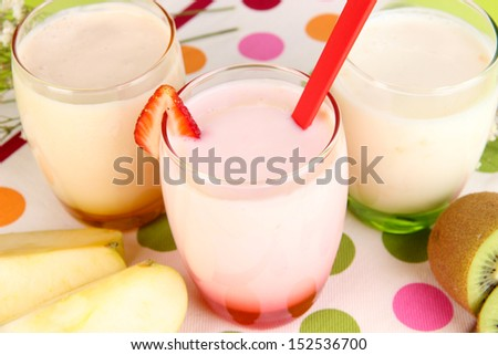Delicious yogurts with fruits in glasses on wooden table close-up