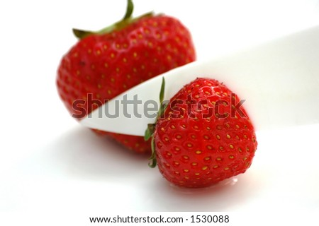 Deliciously red strawberry cut into half with ceramic knife (on white plate) - stock photo