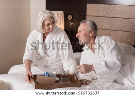 Delighted aged woman holding the breakfast tray