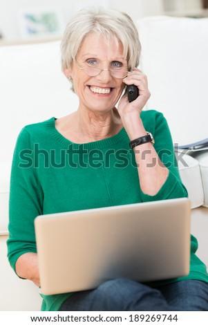 Delighted attractive elderly woman chatting on a mobile phone with her laptop balanced on her knee smiling happily at the camera