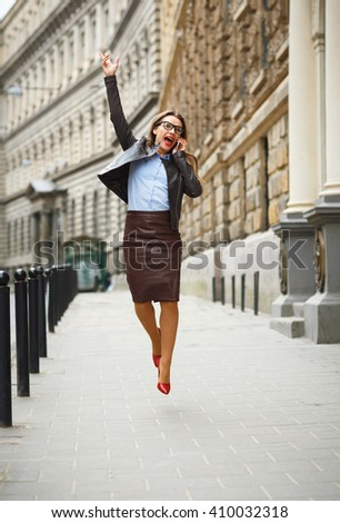 Delighted business woman jumping for joy while talking on the smart phone on the street