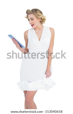 Delighted fashion blonde model looking at a tablet pc on white background - stock photo