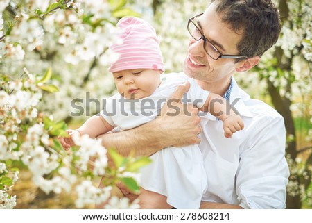 Delighted father hugging his beloved child - stock photo