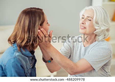Delighted loving senior woman holding cheeks of her daughter