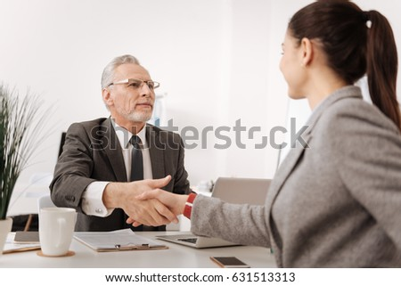 Delighted man and woman shaking hands
