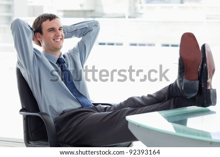 Delighted manager relaxing in his office