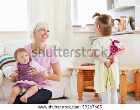 Delighted mother get surprise by her daughters in living-room - stock photo