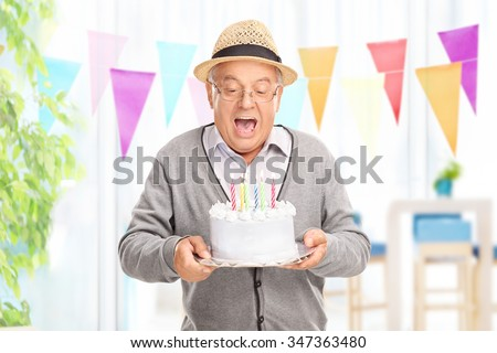 Delighted senior gentleman blowing candles on his birthday cake at home - stock photo