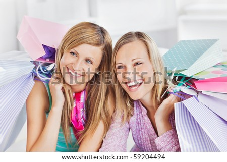 Delighted two women holding shopping bags smiling at the camera at home - stock photo