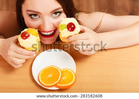 Delighted woman hiding behind table sneaking and eating delicious cake with sweet cream and fruits on top. Appetite and gluttony concept.