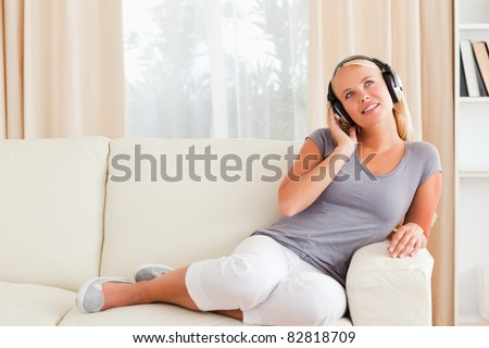 Delighted woman listening to music in her living room