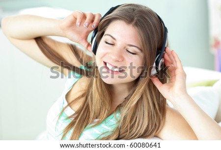 Delighted woman listening to music with headphones on a sofa at home