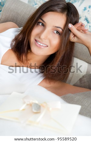 Delighted woman reading a valentine greeting card with heart and ribbon lying on the sofa at home. - stock photo
