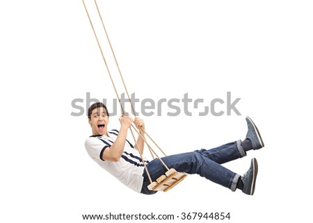 Delighted young guy swinging on a wooden swing and looking at the camera isolated on white background - stock photo