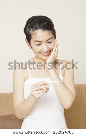 delighted young woman looking on pregnancy test