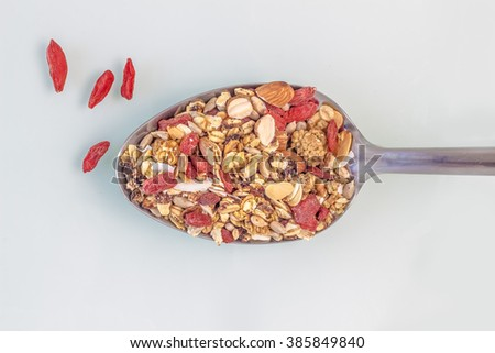 Delightful Cereal and fruit Salad spoon ready to serve. Oats, nuts and overflowed goyi berries. zenith angle of a food spoon isolated. - stock photo