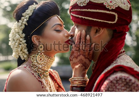 Delightful Indian bride holds her hands painted with mehndi over groom's face while she kisses him