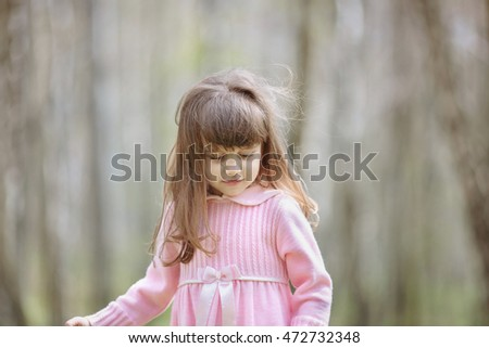 Delightful little child looks down while standing in the forest