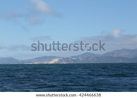 Delightful sea landscape with blue surface of the water, magic feather clouds on the sky over mountain in Kaikoura,New Zealand
