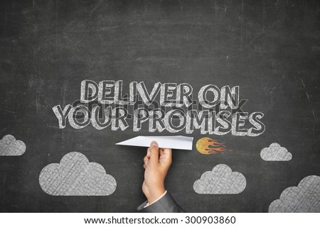 Deliver your promises concept on black blackboard with businessman hand holding paper plane - stock photo