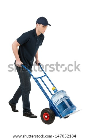 Delivering water. Cheerful young going carrying a hand truck with water jug on it while isolated on white - stock photo