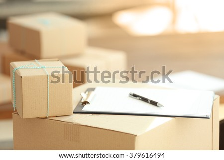 Delivery concept. Group of parcels with clipboard, close up - stock photo