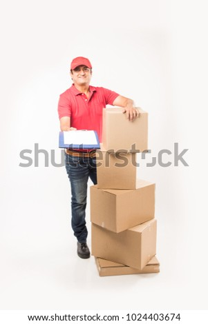 Delivery Concept - Portrait of Happy Indian or delivery man in red or green uniform walking or jumping or checking or presenting cardboard box with copy space