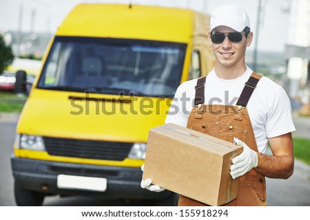 delivery courier man in front of cargo van delivering package parcel carton box - stock photo