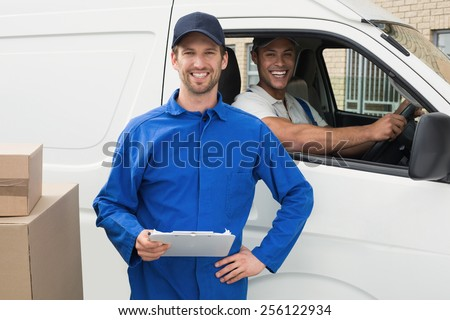 Delivery driver checking his list on clipboard with client outside the warehouse - stock photo