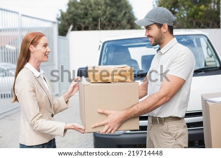 Delivery driver passing parcels to happy customer outside the warehouse - stock photo