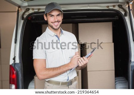 Delivery driver smiling at camera beside his van in a large warehouse - stock photo