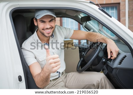 Delivery driver smiling at camera in his van outside the warehouse - stock photo
