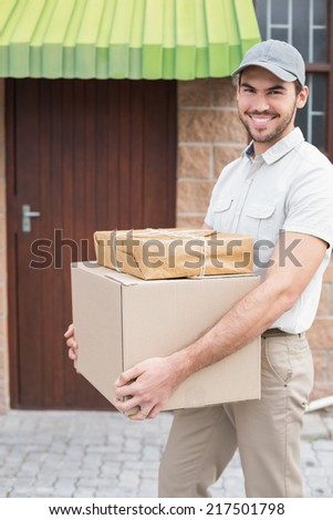 Delivery driver walking with parcels outside the warehouse - stock photo