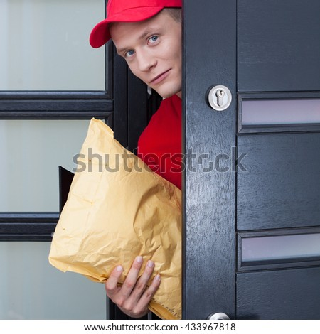 Delivery guy coming through the front door - stock photo