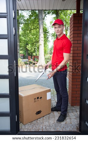 Delivery guy leaving a large package at doorstep - stock photo