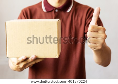 Delivery man carrying a cardboard box giving thumbs up - stock photo