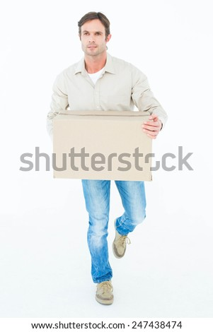 Delivery man carrying cardboard box while walking against white background - stock photo