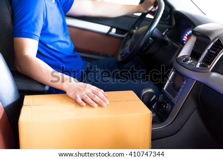 Delivery man driving a truck with cardboard package on the front seat - stock photo