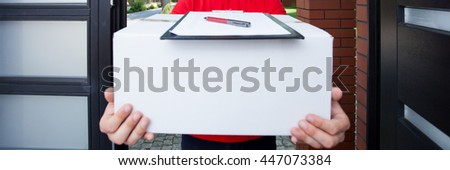 Delivery man giving a parcel to a client - stock photo