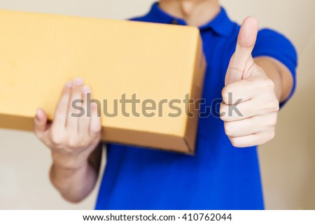 Delivery man giving thumbs up as he carries a package isolated on white background (Focus on Hands) - stock photo