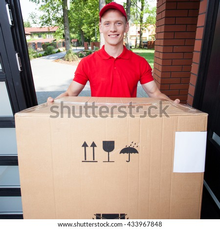 Delivery man handing in a large cardboard box - stock photo