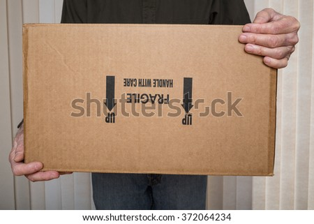 "Delivery man holding a""fragile, handle with care"" package upside down. - stock photo"