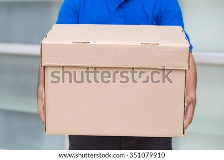 Delivery man holding a parcel box - stock photo